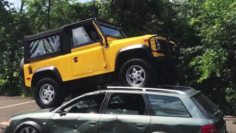 Un tipo pasa por encima de dos coches con su Defender
